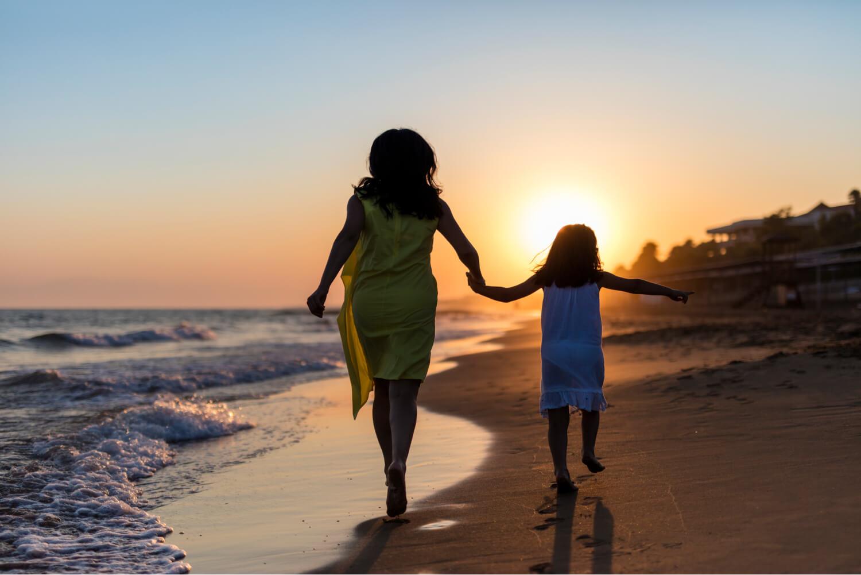 niña y señora caminando en la playa